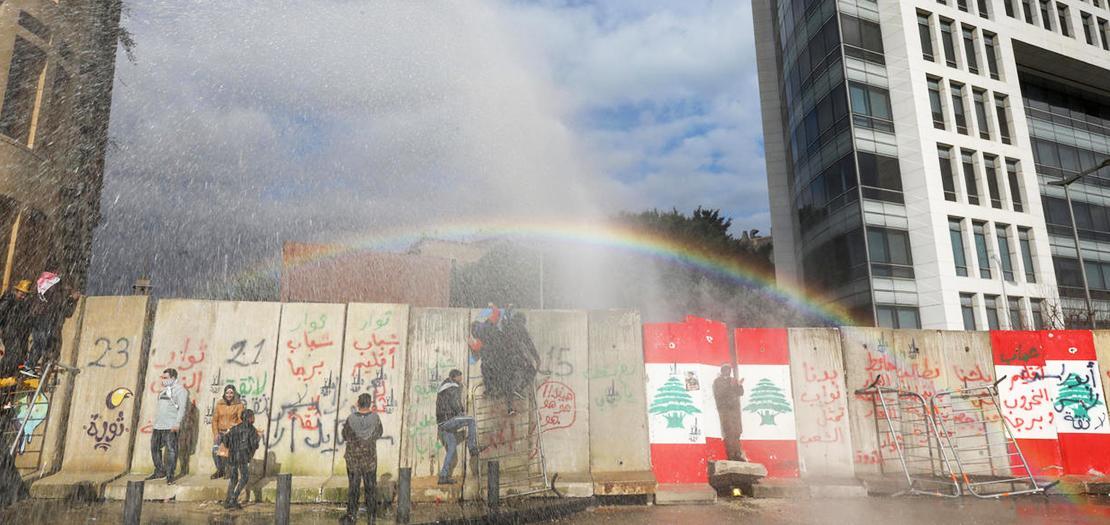 شرطة مكافحة الشغب ترش المياه على المتظاهرين المناهضين للحكومة خلال مظاهرة احتجاج ضد تصويت مجلس النواب على منح الثقة لحكومة رئيس الوزراء اللبناني المكلف حسان دياب، في العاصمة بيروت (أ ف ب)