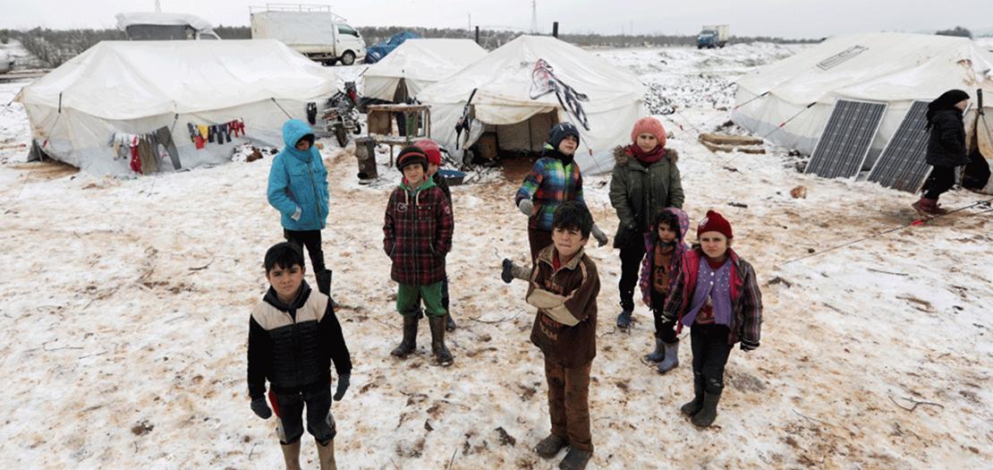 أطفال من النازحين داخليا يلعبون في الجليد بالقرب من خيام في معسكر، الخميس (رويترز)
