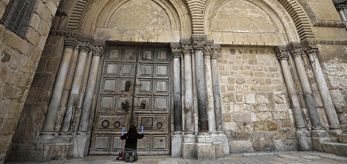 سيدة تركع مصلية أمام كنيسة القيامة بالقدس بعد إغلاقها لاحتواء انتشار وباء الفيروس التاجي