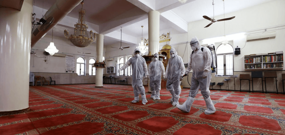 متطوعون فلسطينيون يرتدون ملابس واقية أثناء تطهير مسجد في القدس للمساعدة في مكافحة فيروس كورونا، 16 آذار 2020 (رويترز)