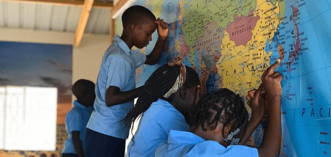 أطفال من موزمبيق يصلّون من أجل دول العالم المصابة، وكل طفل يضع يده على خارطة دولة ويصلي لها