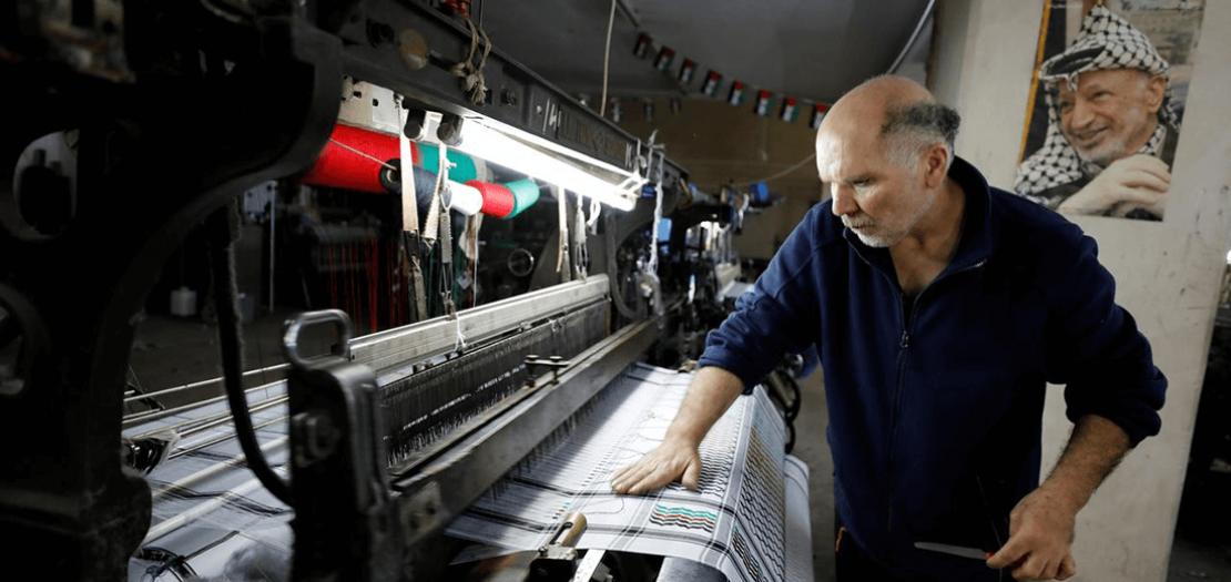 رجل يعمل في مصنع للكوفية الفلسطينية التقليدية في الخليل بالضفة الغربية، 7 أيار 2020 (تصوير: موسى قواسمة - رويترز)