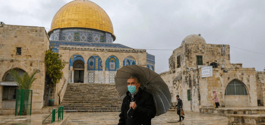 فلسطيني يضع كمامة وقائية من فيروس كورونا المستجد يسير أمام مسجد قبة الصخرة في القدس الشرقية المحتلة في 20 آذار 2020