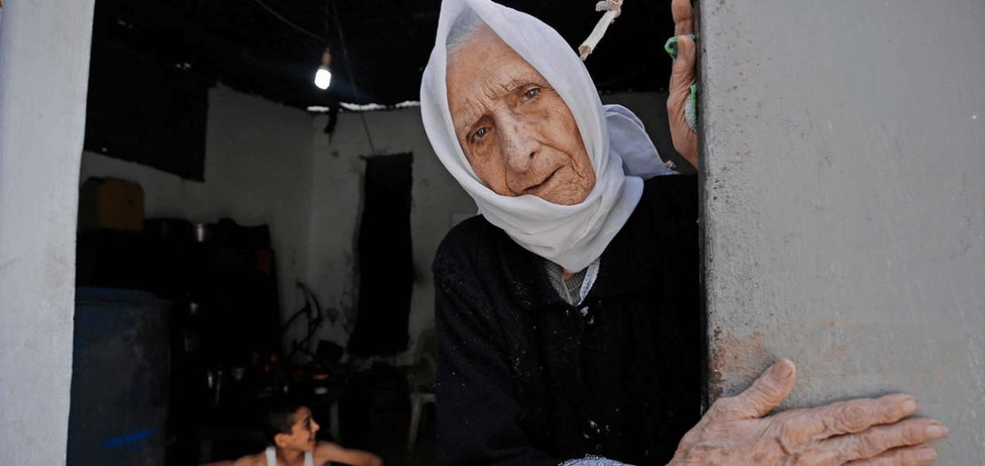 فلسطينية لاجئة عاشت نكبة 1948 عند مدخل منزلها في مخيم الشاطئ للاجئين في مدينة غزة في 15 أيار 2020، حيث احيا الفلسطينيون الذكرى 72 لنكبة داخل منازلهم بسبب جائحة كورونا