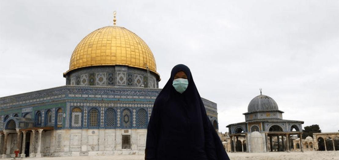 امرأة تضع كمامة للوقاية من فيروس كورونا أمام قبة الصخرة في القدس (13 آذار 2020)