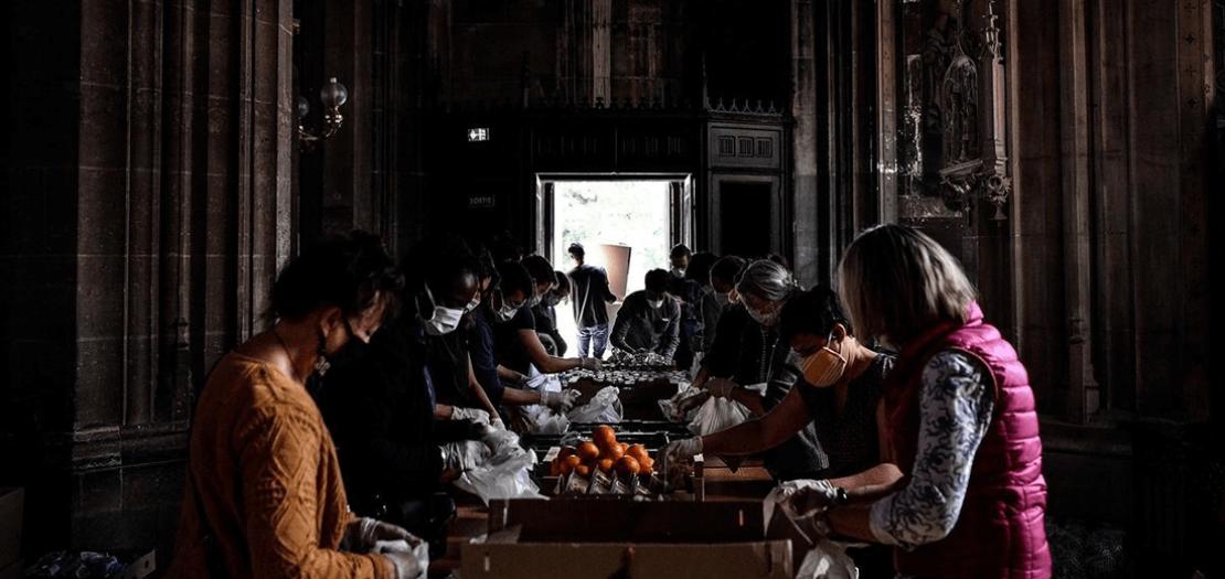 متطوعون يجمعون الطعام للأسر المتضررة بسبب تفشي فيروس كورونا في فرنسا بكنيسة سانت برنار لاشابل بباريس، 6 أيار 2020 (أ ف ب)