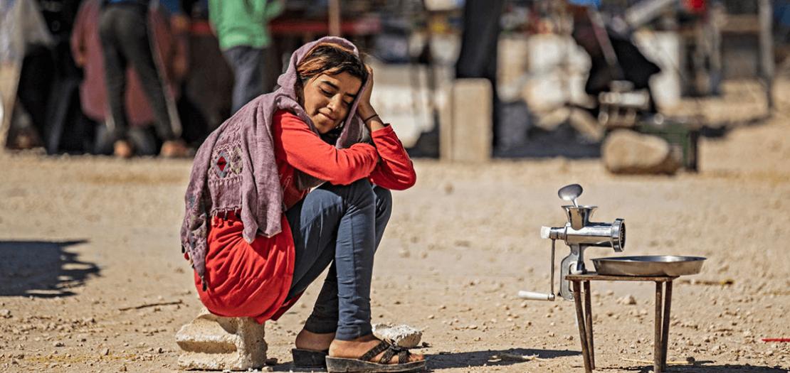 طفلة تنتظر زبائن لطحن الحبوب في مخيم للنازحين في الحسكة