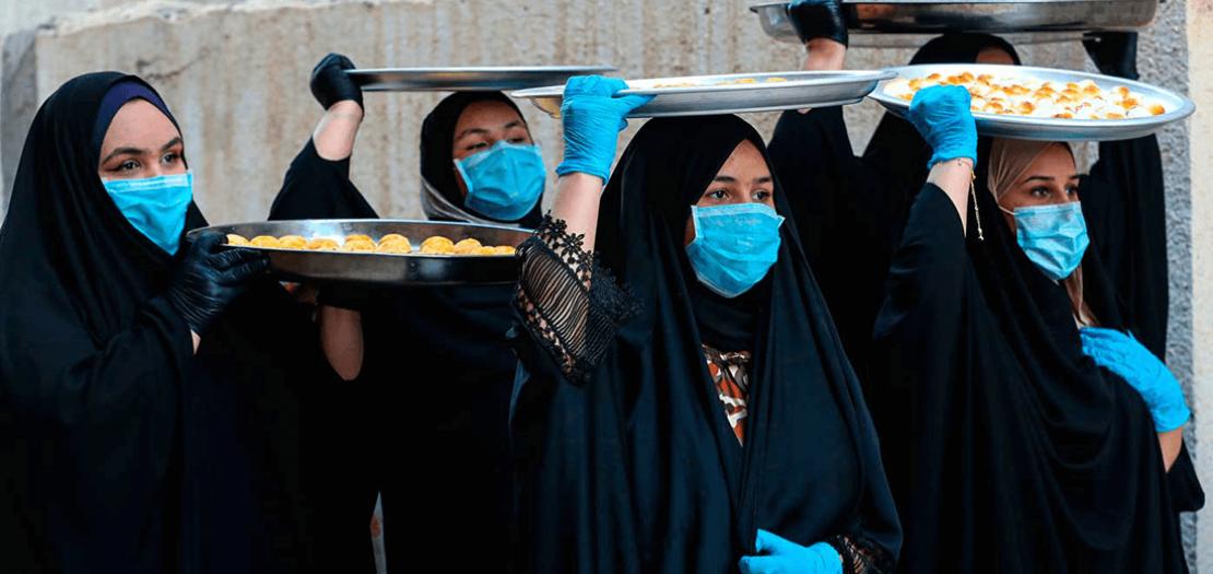 نساء عراقيات يرتدين كمامات واقية للحماية من انتشار فيروس كورونا، ويضعن على رؤوسهن صواني كعك عيد الفطر، في مدينة البصرة العراقية (أ ف ب)
