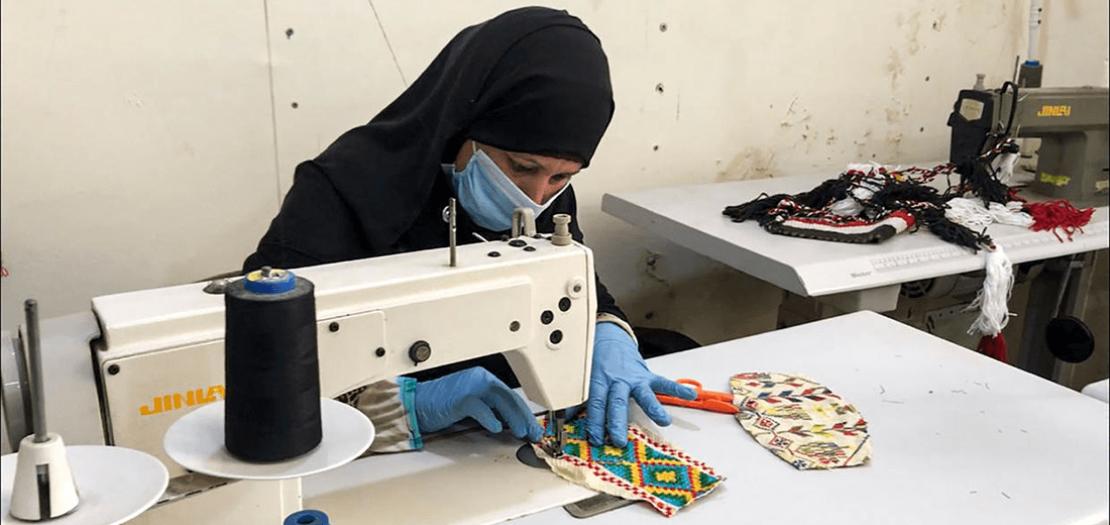 صورة موزعة من مؤسسة الفيروز تظهر حائكة تعمل على كمامة في مشغل في سيناء بمصر