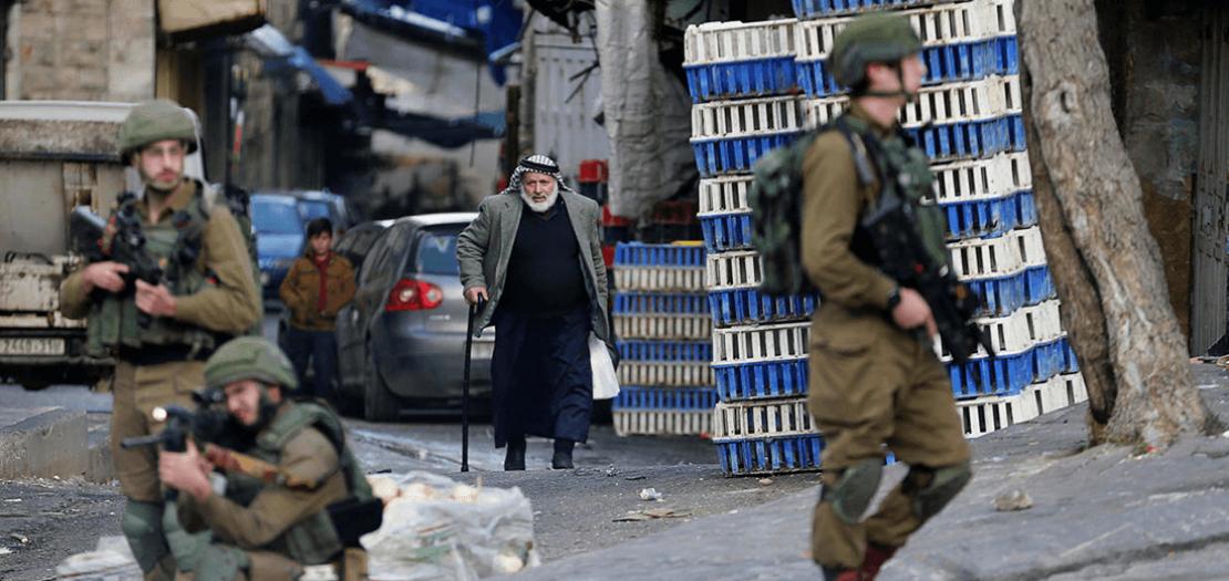 مسن فلسطيني يمشي بالقرب من جنود إسرائيليين أثناء قمعهم لمظاهرة احتجاجًا على خطة الرئيس الأمريكي دونالد ترامب للسلام في الشرق الأوسط، في الخليل في الضفة الغربية المحتلة، 6 شباط 2020