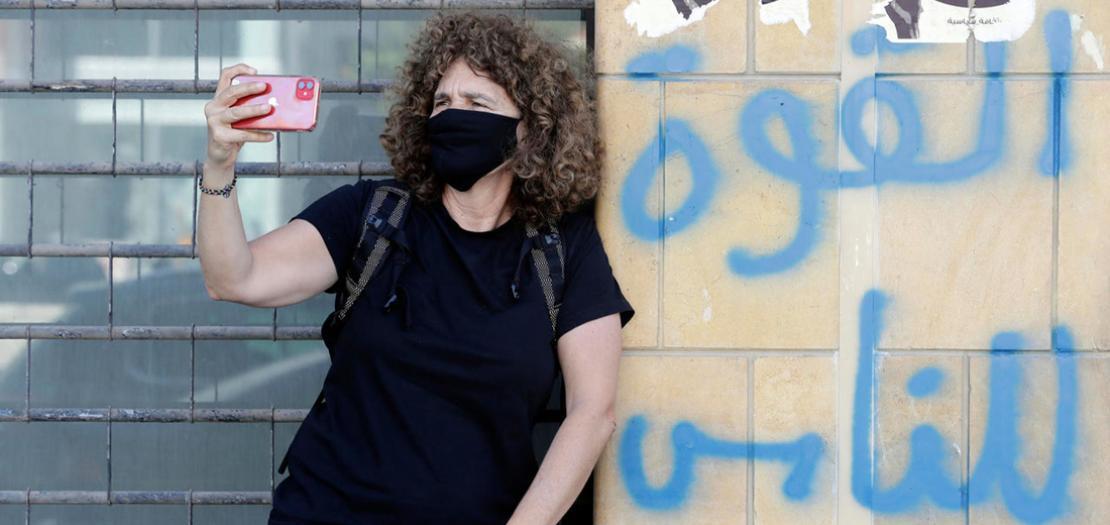 المخرجة اللبنانية كارول منصور تستخدم هاتفها للتصوير وتضع كمامة في بيروت