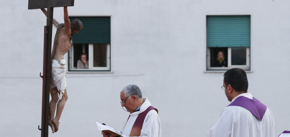 """كاهن إيطالي يترأس صلاة """"درب الصليب"""" فوق سطح كنيسته في نابولي، فيما يشارك السكان عبر شرفات منازلهم، 30 آذار 2020"""