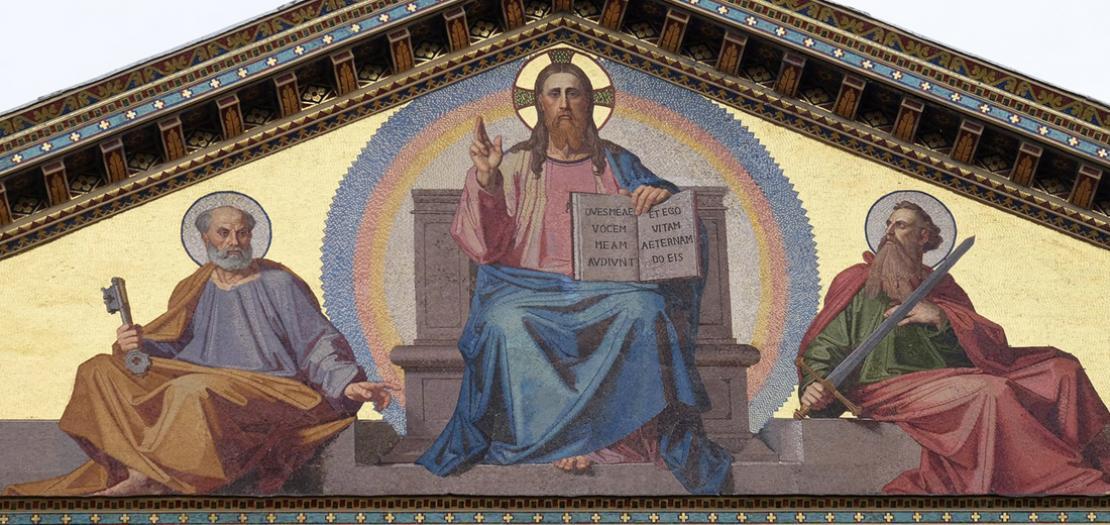 """فسيفساء جميلة تغطي واجهة كنيسة القديس بولس خارج الأسوار البابويّة في روما، وفيها يظهر في المنتصف السيد المسيح """"المعلم""""، والقديس بطرس (يسار) والقديس بولس"""