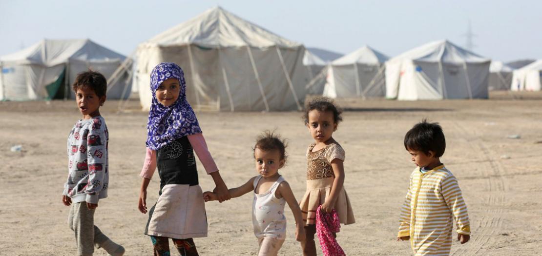 أطفال يمشون في مخيم للنازحين في مأرب باليمن، 8 آذار 2020 (تصوير: علي عويضة - رويترز)