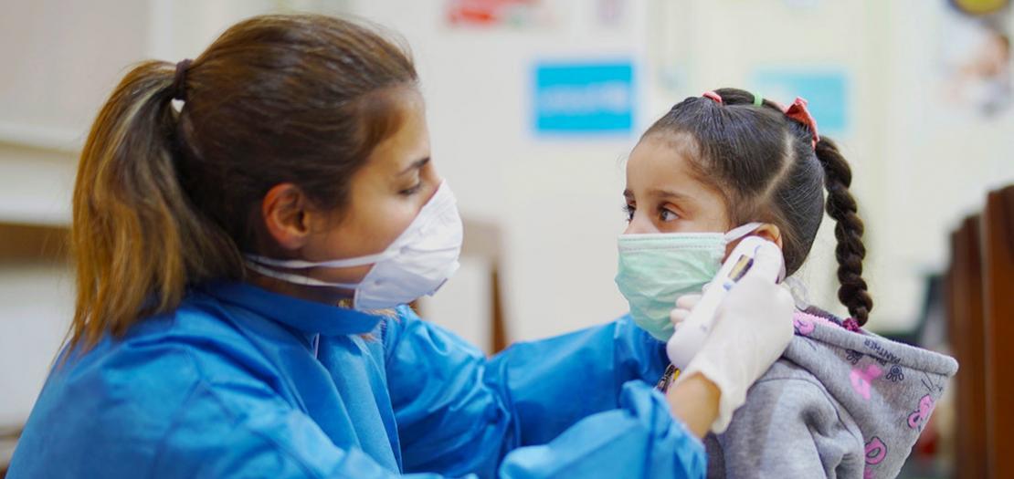 ممرضة تقيس درجة حرارة طفلة في مركز للرعاية الصحية الأولية في بيروت، لبنان، أثناء تفشي COVID-19.