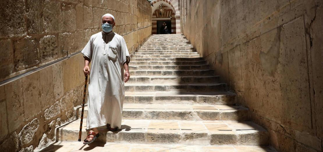 فلسطيني يضع كمامة واقية أثناء مغادرته الحرم الإبراهيمي بعد أداء صلاة الجمعة في مدينة الخليل جنوب الضفة الغربية المحتلة، 26 حزيران 2020
