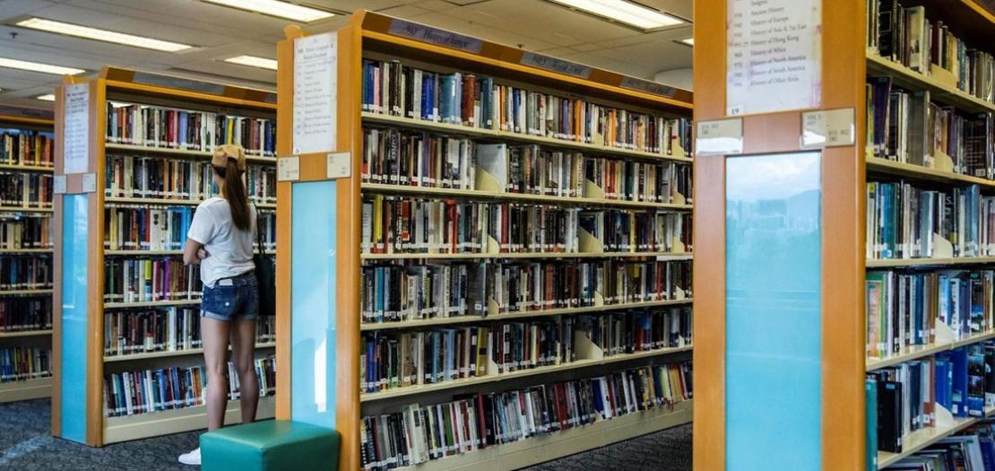 امرأة تفحص كتبًا في مكتبة عامة في هونغ كونغ في 4 تموز 2020