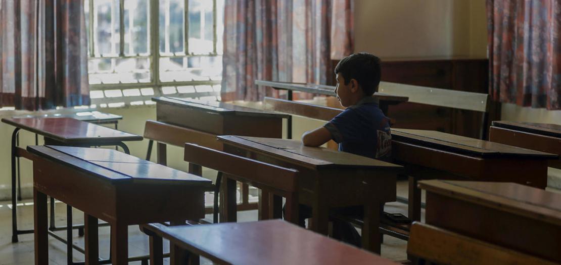 طفل لبناني يجلس وحيدًا في غرفة صف بمدرسة في مدينة زحلة