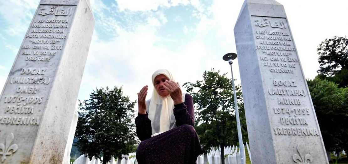 البوسنية المسلمة ميرا ديوغاز (71 عامًا) الناجية من مجزرة سريبرينيتسا تصلي على أرواح أبنائها في نصب بوتوتشاري، 3 تموز 2020