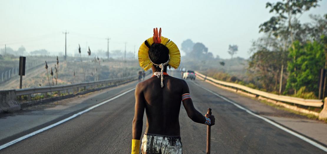 فرد من قبيلة كابابو يسير وسط طريق سريع مغلق أثناء وقفة احتجاجية على مشارف محلة نوفو بروغريسو في ولاية بارا في البرازيل، 17 آب 2020