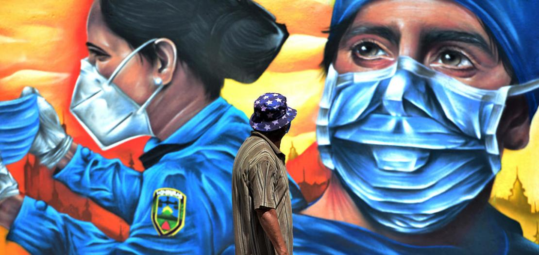 رجل يمرّ أمام لوحة جدارية تُظهر شرطية وعامل صحي في تيغوسيغالبا في هندوراس، 14 أيلول 2020
