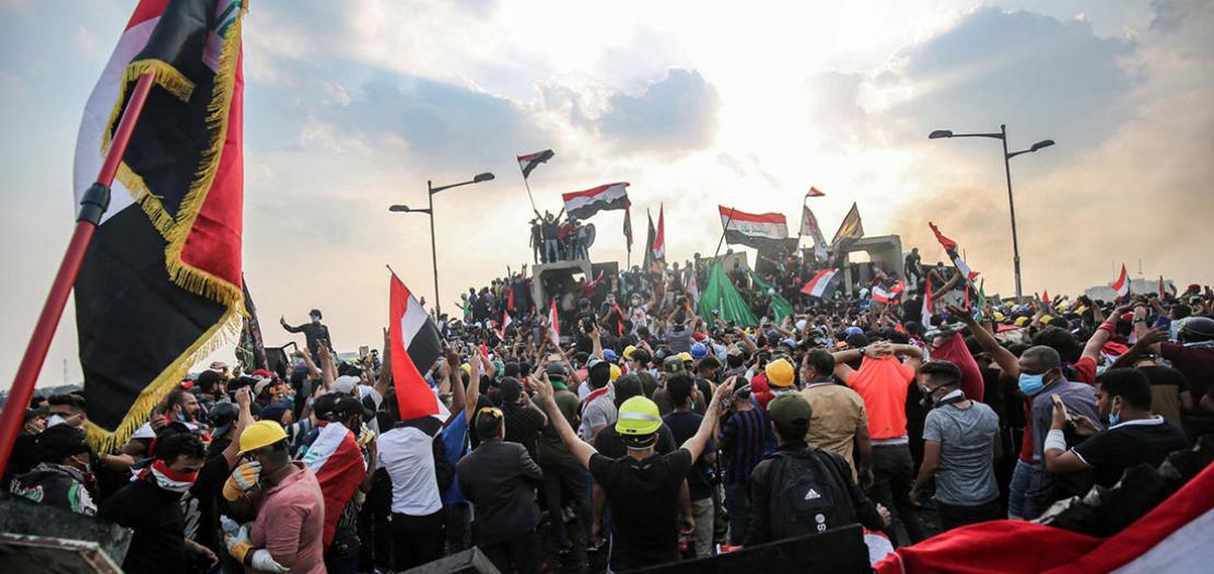 صورة من الارشيف لمتظاهرين عراقيين يلوحون باعلام البلاد في العاصمة بغداد، 29 تشرين الأول 2019