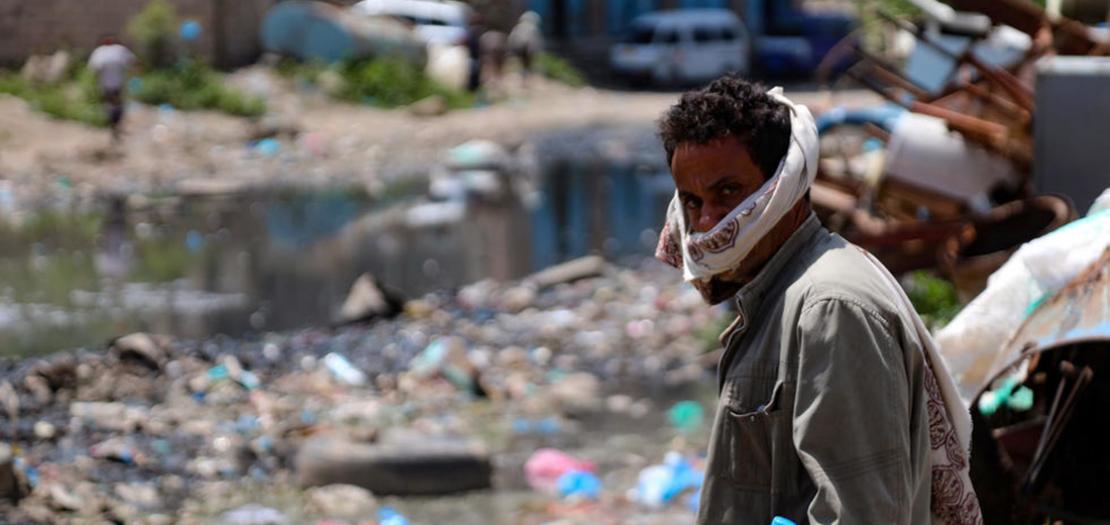 رجل يعبر شارعا تجري فيه مياه الصرف الصحي وتكسوه القمامة في مدينة تعز اليمنية في 19 أيلول 2020