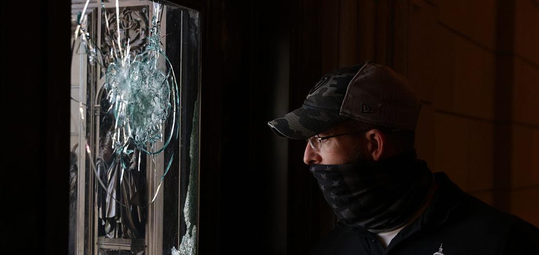 فني يتفقد مدخلاً متضررًا في مبنى الكابيتول بعد الهجوم الذي تعرض له المبنى مؤخرًا