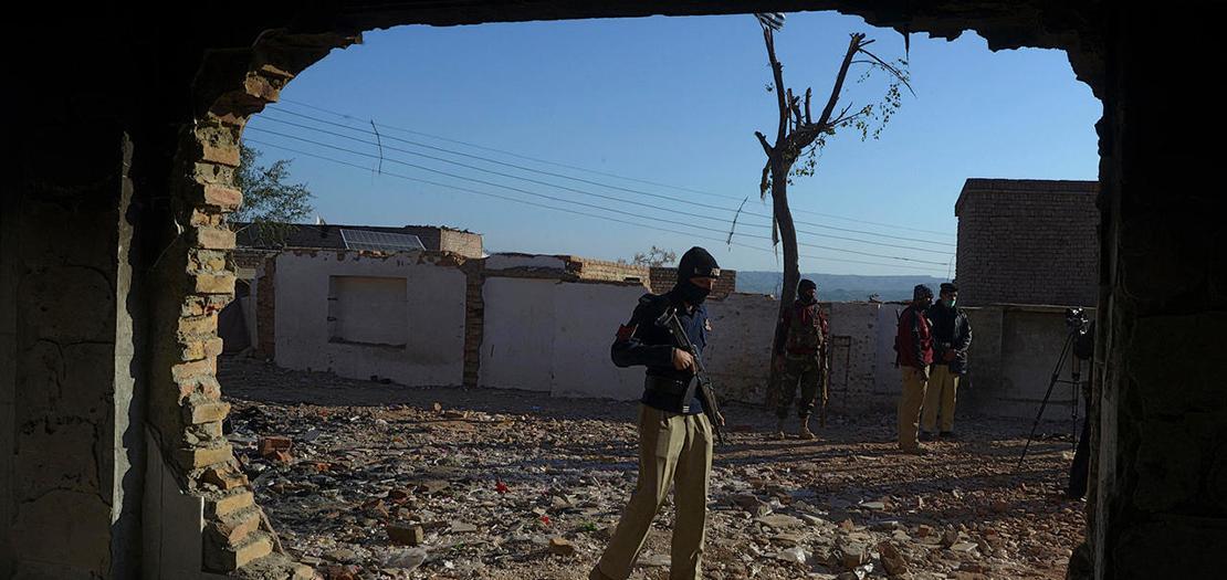 شرطي يقف أمام معبد هندوسي أحرقه حشد غاضب قبل يوم في قرية كرك على بعد 160 كلم جنوب شرق بيشاور، 31 كانون الأول 2020