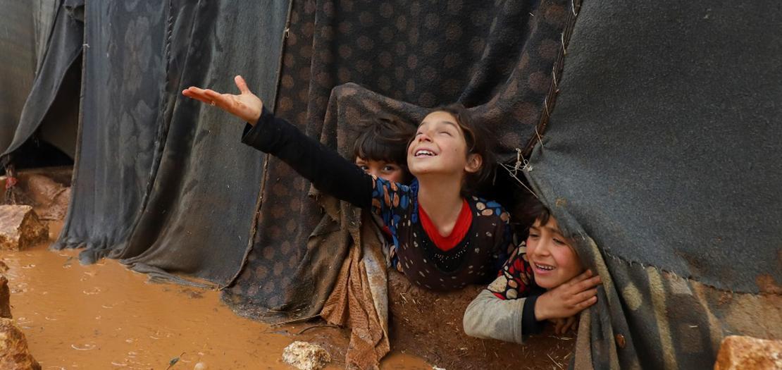 رغم كل الألم، طفلة سورية تبتسم وتمدّ يدها للمطر. الصورة من مخيم أم جرن في ضواحي إدلب بسورية بعد هطول المطر الذي تسبب بسيول وغرق مئات الخيام وتشرّد سكّانها (أ ف ب)