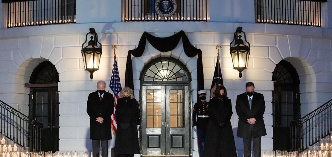 الرئيس الأميركي جو بايدن وزوجته جيل، وعن يسارهما نائبة الرئيس كامالا هاريس وزوجها دوغ إيمهوف، أثناء وقوفهم دقيقة صمت حدادًا على ضحايا كوفيد-19 أمام البيت الأبيض، 22 شباط 2021