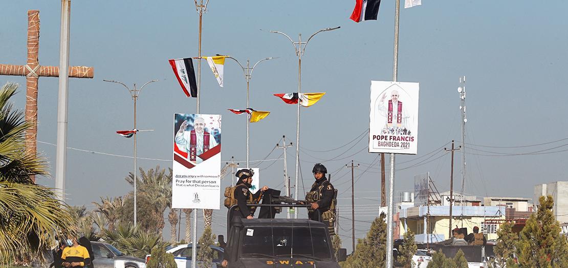 قوات أمن عراقية تمرّ بجوار أعلام الفاتيكان والعراق وملصقات ترحيبية بزيارة البابا فرنسيس، في أحد شوارع قرقوش، 22 شباط 2021