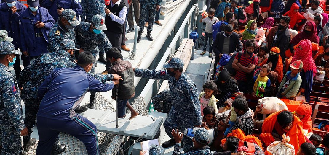 أفراد من البحرية البنغلاديشية يساعدون طفلاً لاجئًا من الروهينغا على النزول من سفينة تابعة للبحرية عند وصولهم إلى جزيرة بهاسان شار في منطقة نواكالي، بنغلاديش، 29 كانون الأول 2020