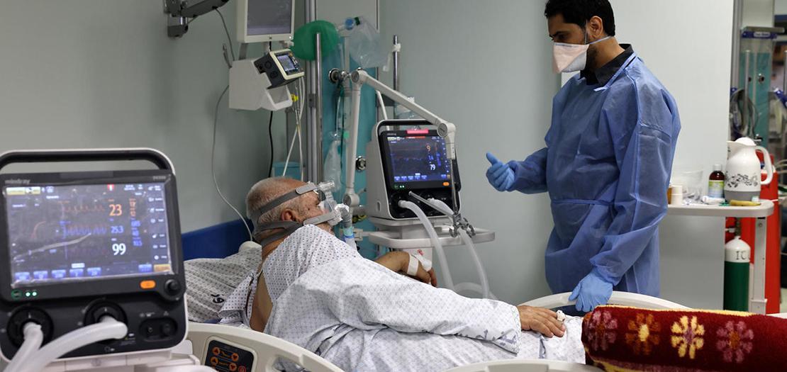 المصاب الفلسطيني بفيروس كورونا حسين الحاج (71 عاما) يتحدث إلى الممرض في غرفة العناية المكثفة في مستشفى الصداقة الفلسطيني التركي في 22 نيسان 2021