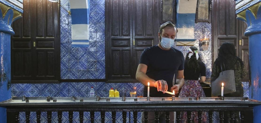 يهودي تونسي يشعل شمعة ضمن مراسم الحج إلى كنيس الغريبة بجزيرة جربة، أقدم معبد يهودي في أفريقيا، 26 نيسان 2021