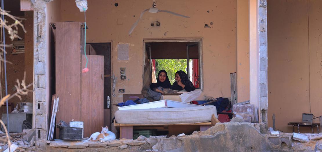 سيدتان فلسطينيتان في منزلهما الذي دمره قصف إسرائيلي في بيت حانون في شمال قطاع غزة، 21 أيار 2021