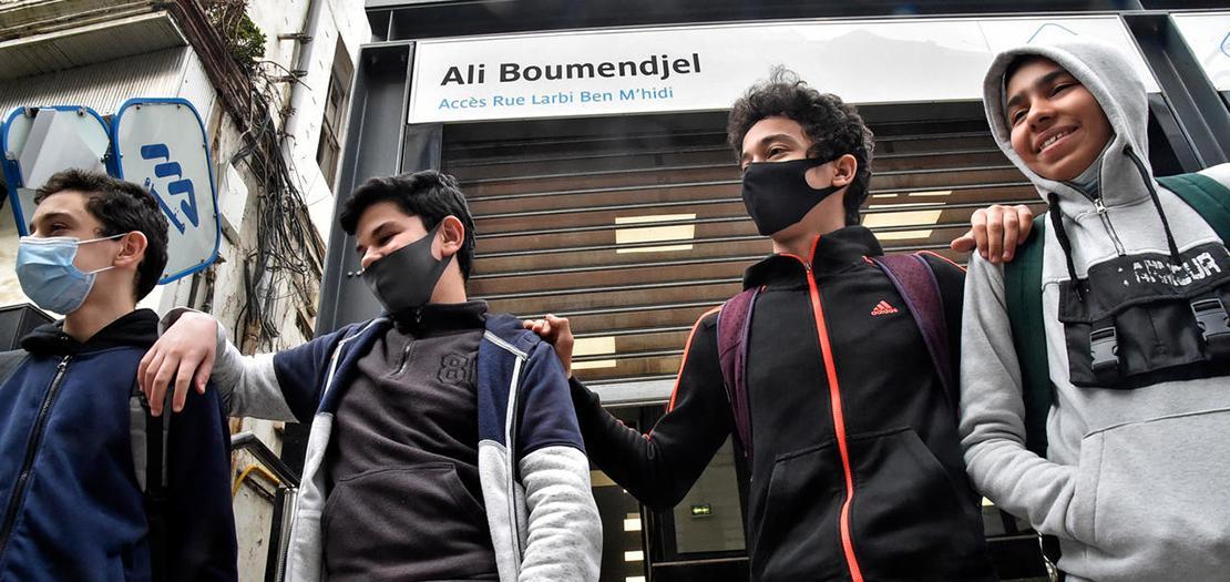 صورة بتاريخ 4 آذار في محطة مترو بالجزائر تظهر شبانًا أمام لافتة طريق تحمل اسم المحامي والناشط الجزائري علي بومنجل الذي قتلته القوات الفرنسية خلال حرب الاستقلال