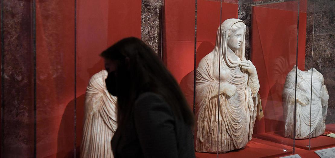 زائرة لمعرض في متحف اللوفر في باريس تطلع على تماثيل منهوبة من مقابر قورينا الأثرية في شرق ليبيا ضبطتها السلطات الفرنسية في مطار رواسي عام 2016 خلال تهريبها من لبنان إلى تايلاند