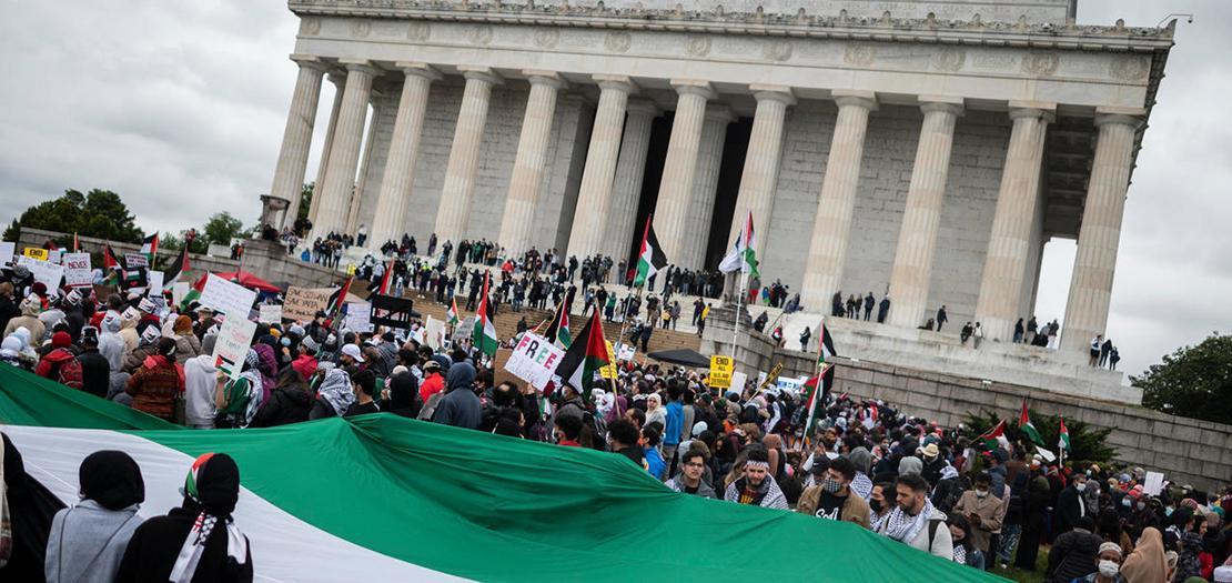 أشخاص يلوحون بالأعلام الفلسطينية، خلال مظاهرة للتعبير عن الدعم لشعب فلسطين، أثناء تجمعهم في نصب لنكولن التذكاري في واشنطن العاصمة، 29 أيار 2021