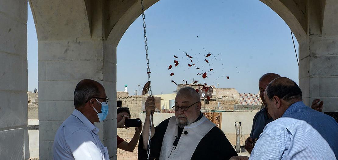 كاهن يقرع جرس كنيسة مار توما السريانية المسيحية في الموصل شمال العراق في 18 أيلول 2021