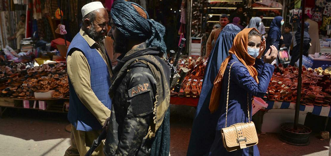 مقاتل من طالبان (وسط) يمر قرب متسوقين في سوق منداوي في كابول في 1 أيلول 2021.