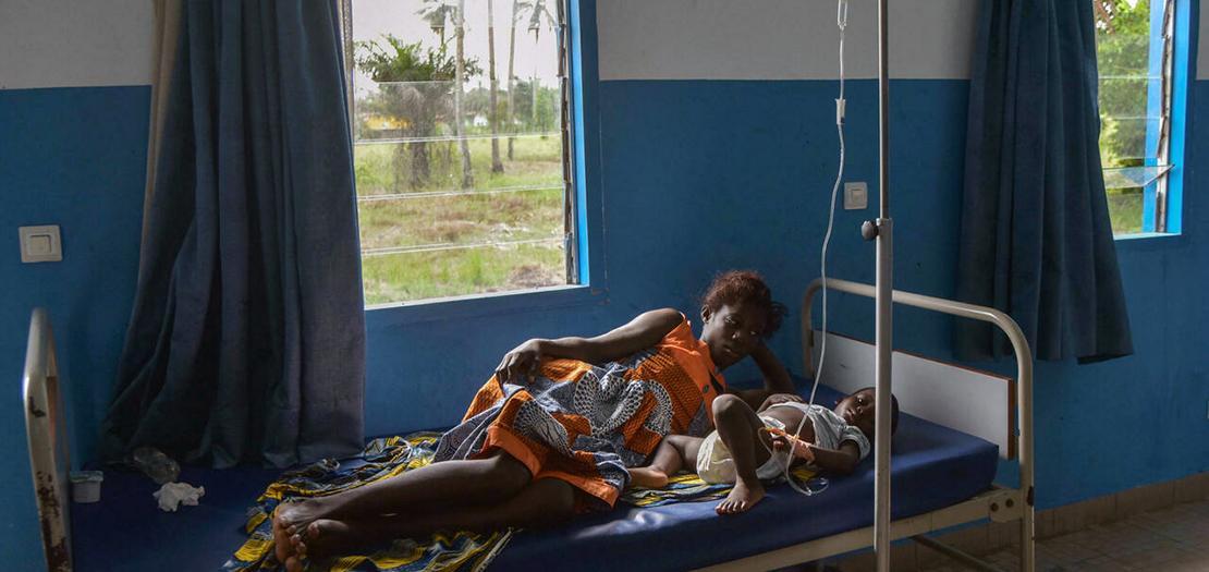 امرأة بجانب طفل مصاب في جاكفيل في ساحل العاج