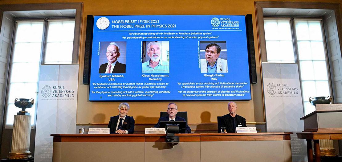 الأمين العام للأكاديمية الملكية السويدية للعلوم سوران هانسون (وسط) وعضوا لجنة نوبل للفيزياء تورس هانز هانسون (يسار) وجون ويتلوفر يجلسون أمام شاشة عليها صور الفائزين الثلاثة بجائزة نوبل للفيزياء في ستوكهولم في الخامس من تشرين الأول 2021